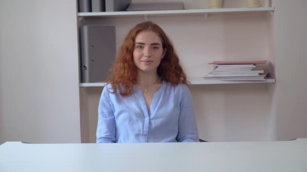 Portrait redheaded lady at working place.