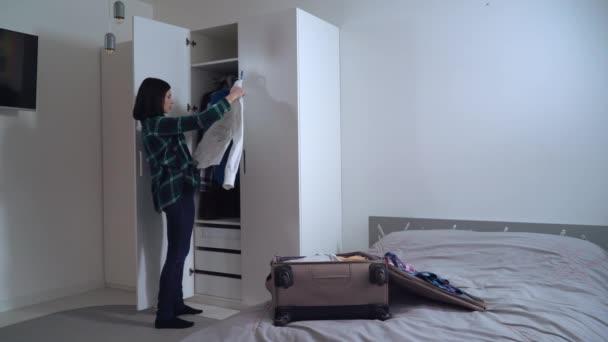 Dívka u skříní plnící košile v sáčku