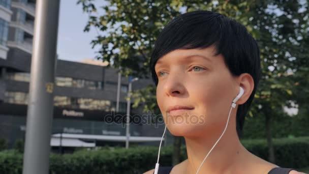 Dívka s sluchátka chůze u moderní budovy