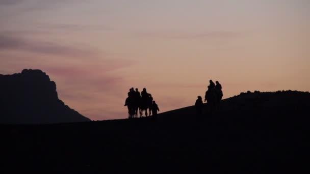 Camel tour arrive at dusk to a Berber camp