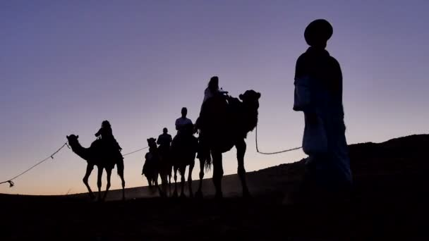 Group of tourist arrive on camels to the Berber camp