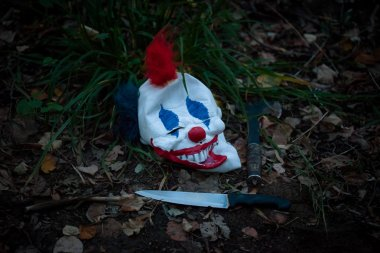 Mask of scary clown on ground in the wood