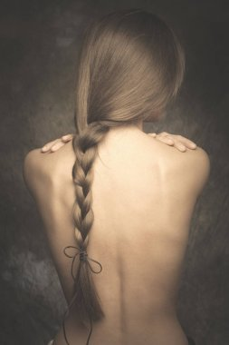 intimate woman portrait bare back and long braid