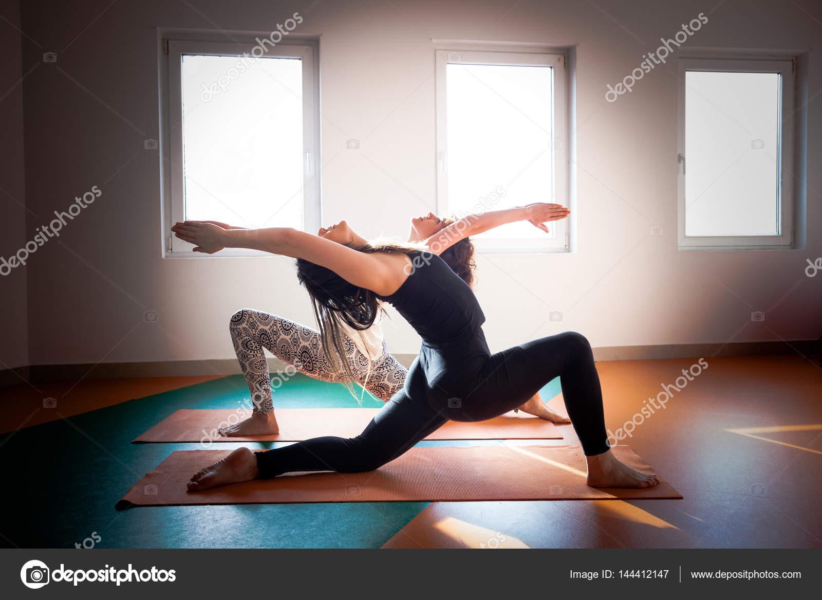 dos mujeres haciendo yoga interior — Foto de stock © cokacoka  144412147 e5ef9aec220e