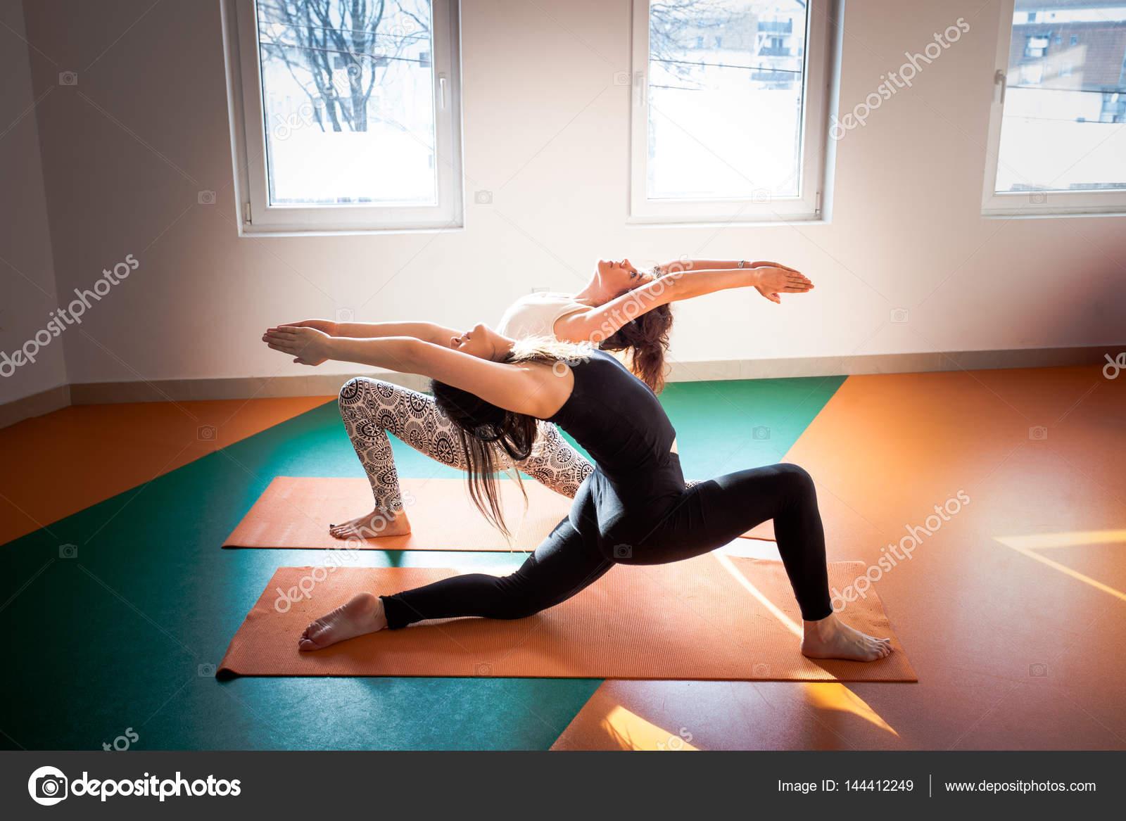Dos mujeres haciendo yoga interior — Foto de Stock 1994828c0a43