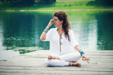 woman practicing yoga breathing technique by the lake