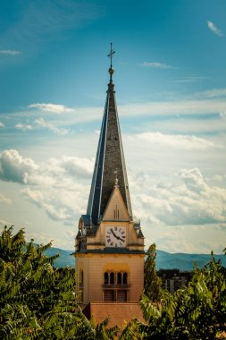 Catholic church clock tower  among tree crowns
