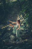 mladá žena cvičím jógu venkovní v korytě malých horských