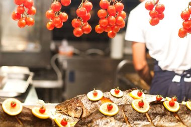 chef prepares fish, seasoned with lemon and cherry tomatoes