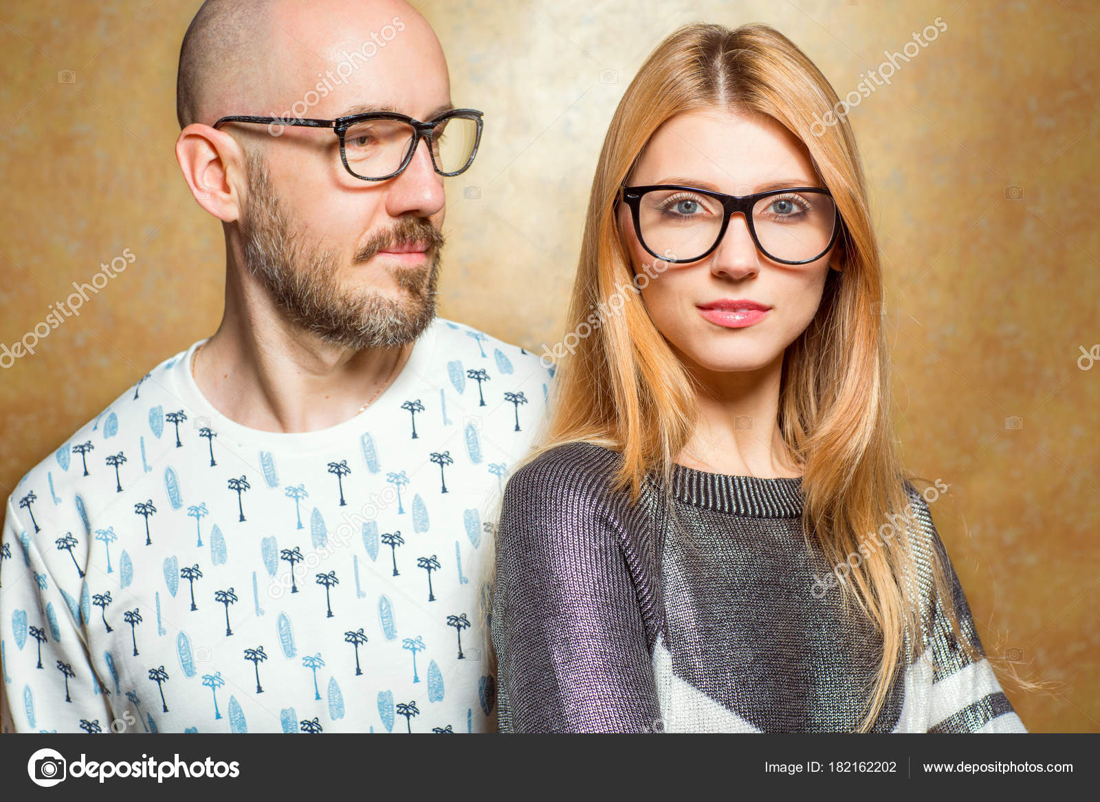 b474e98eefd Fashion hipster couple in love in glasses posing on a gold backg — Stock  Photo