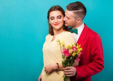 hipster couple in love with a bouquet of flowers in the studio a
