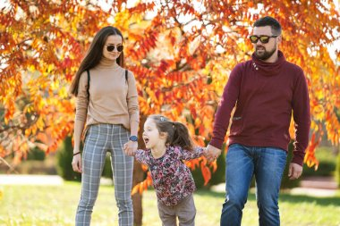 family with daughter walks in autumn park
