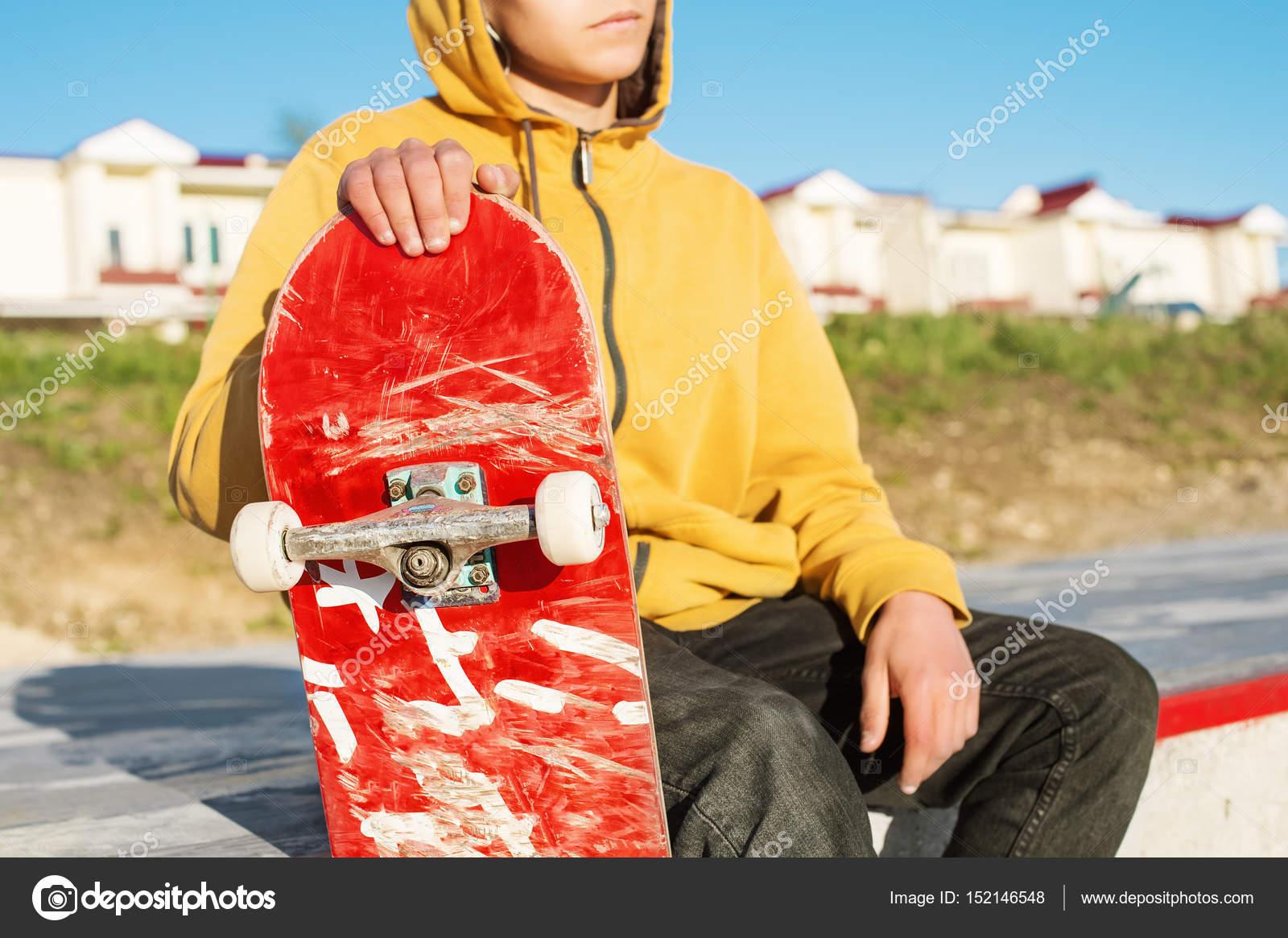 Primer plano de un joven inconformista vestido con una sudadera y jeans  sentado triste en un parque de skate y sosteniendo una tabla de Skate —  Foto de ... 5a449991b2f