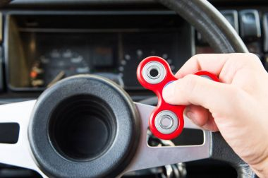 Close-up of a mans hand playing with a spinner while in a traffic jam on the background of the cars interior