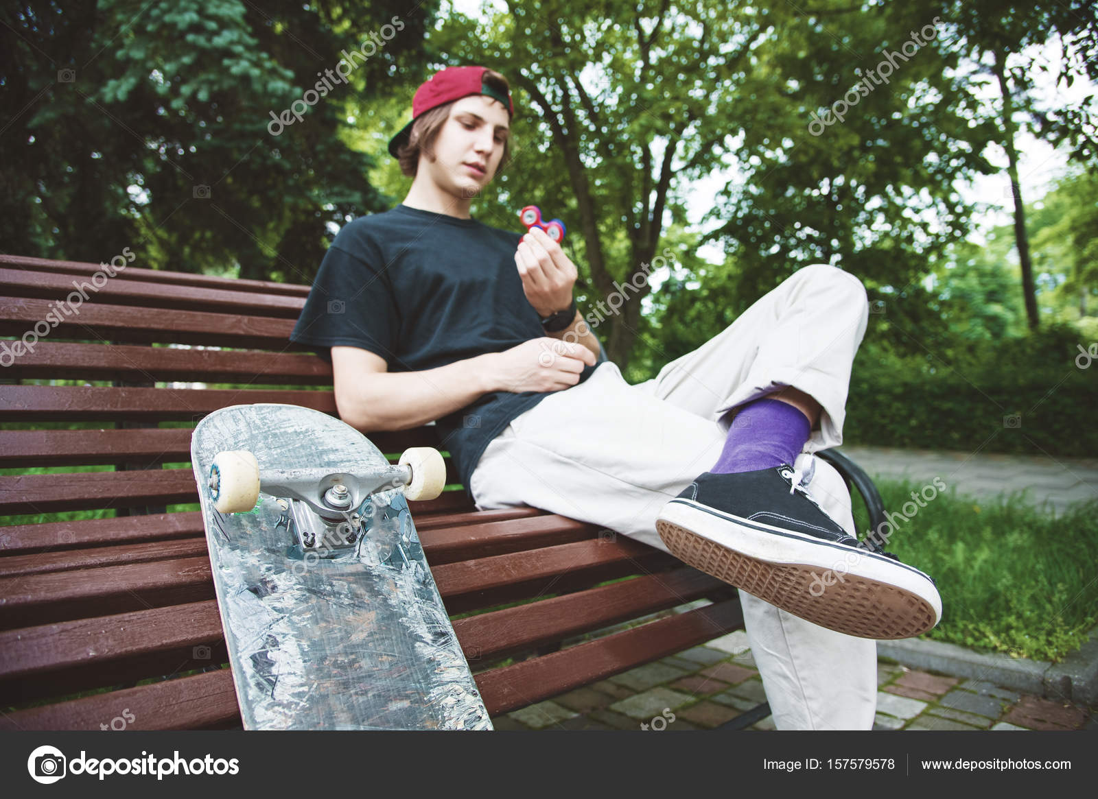 4e63b535c46 A long-haired hipster skater in a cap sits on a bench and turns a spineless  spinner next to a skateboard — Photo by ...