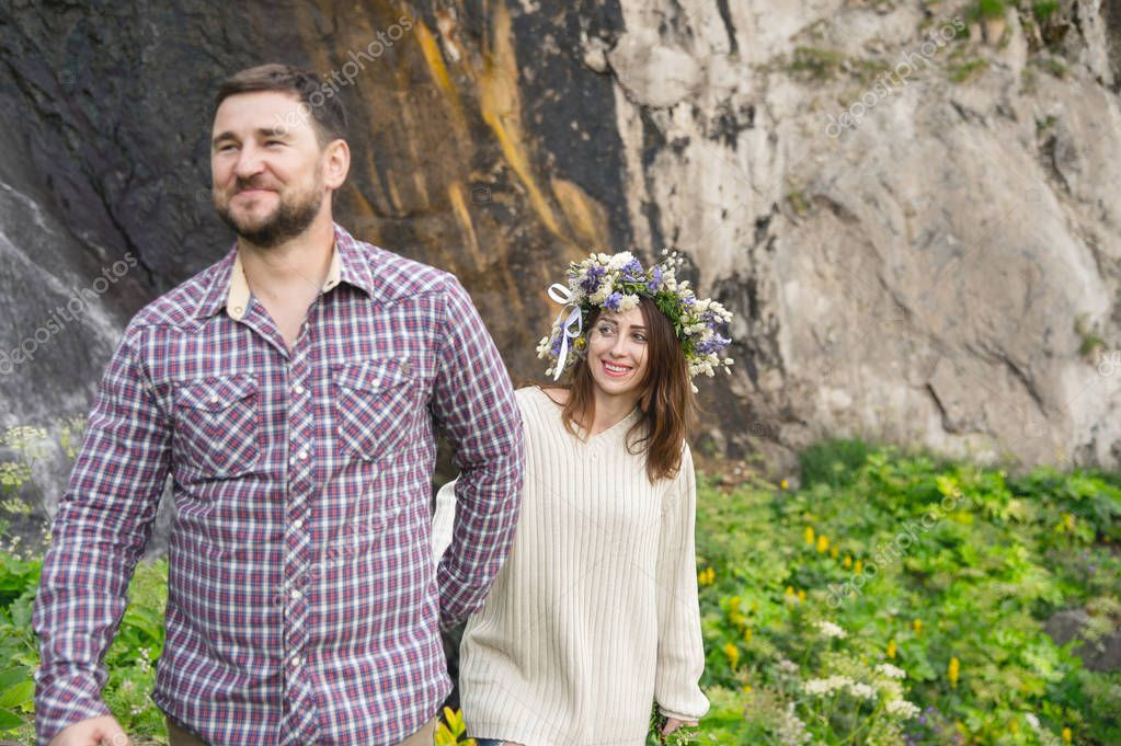 Hipster with a beard leads his bride in nature