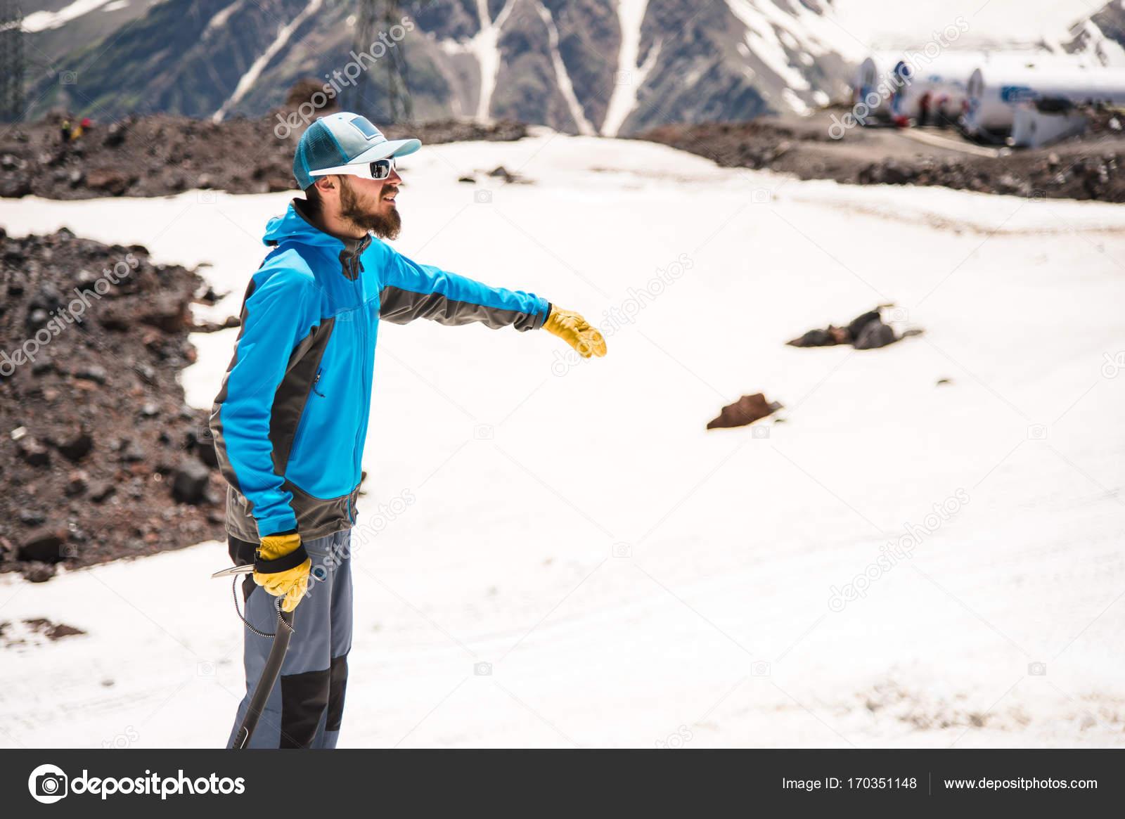 812f0434de Formation de corriger glisser sur une pente ou d'un glacier à l'aide d'une  hache de glace. Un jeune guide avec une barbe explique à son groupe comment  ...