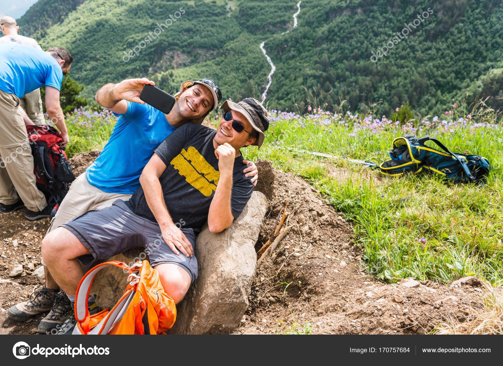 Vrienden nemen selfie zittend op rots — Stockfoto