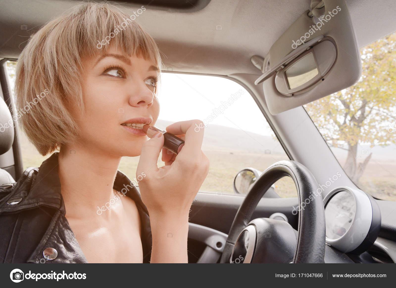 Linda chica rubia con el pelo corto para colorear labios mientras ...