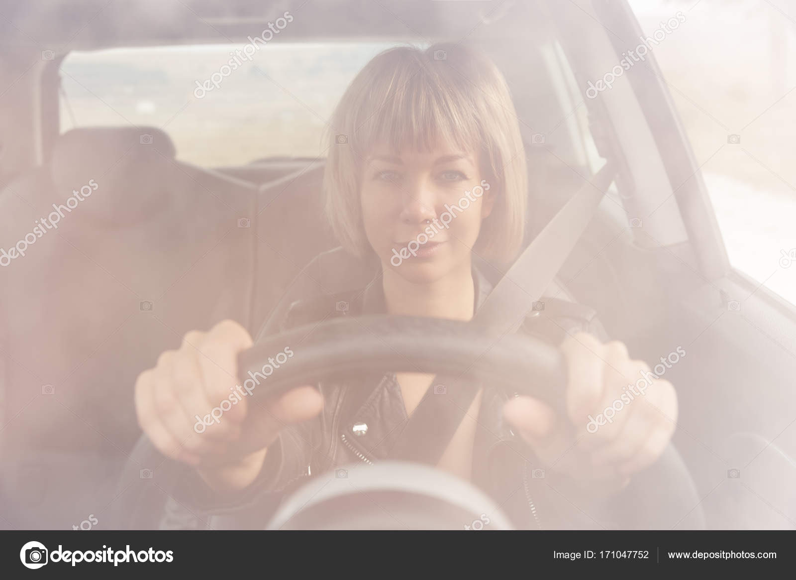 Cute Girl With Short Haircut Sits Behind The Wheel Of A Small Car