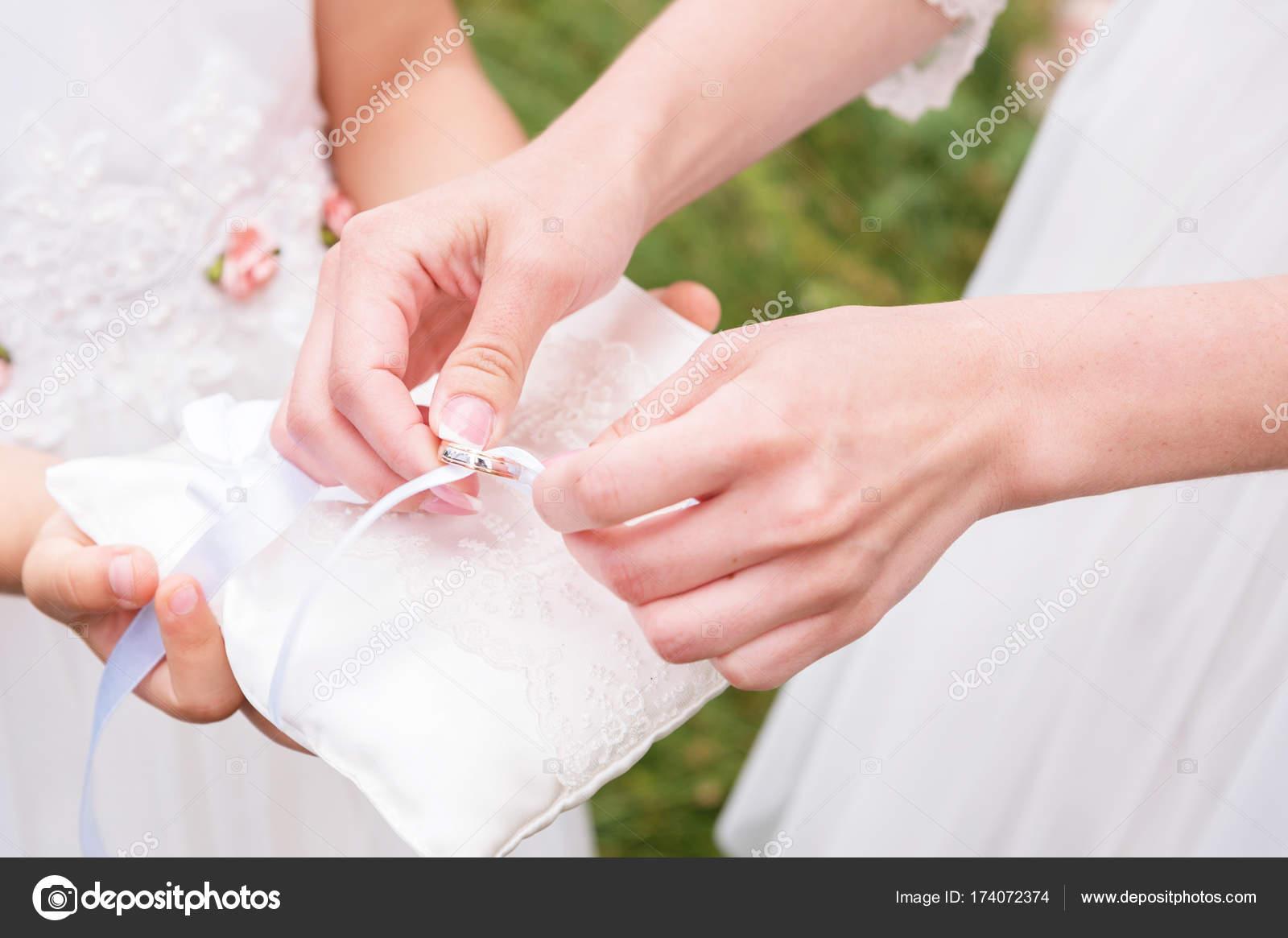 Dama de honor de manos de primer plano en vestido blanco lleva con ...