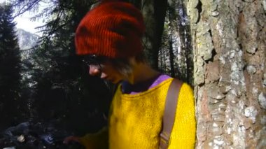 An active healthy hipster girl-photographer with a camera in her hands walks through the forest. The girl is taking pictures. Low key 60 FPS slow motion. GoPro 6 Black with a three-axis antimicrobial