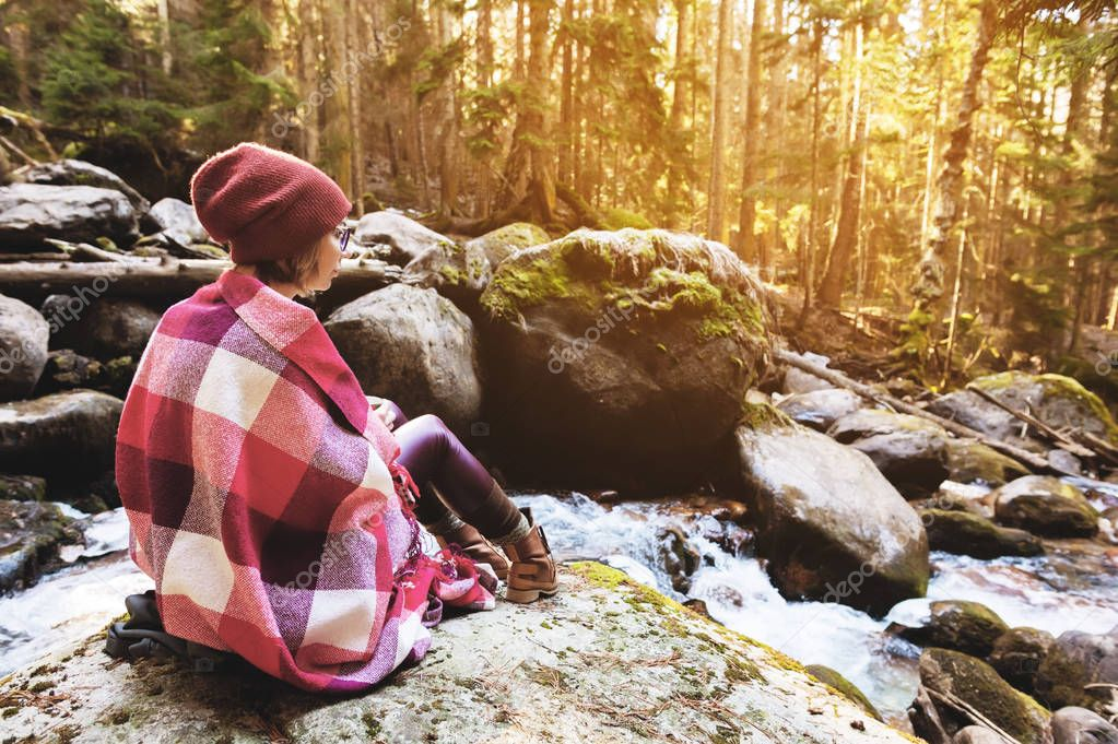 A pretty hipster girl with a plaid plaid on her shoulders in a hat and a yellow sweater and glasses with a mug of coffee in her hands looks at a mountain river sitting on a rock in a pine forest. The