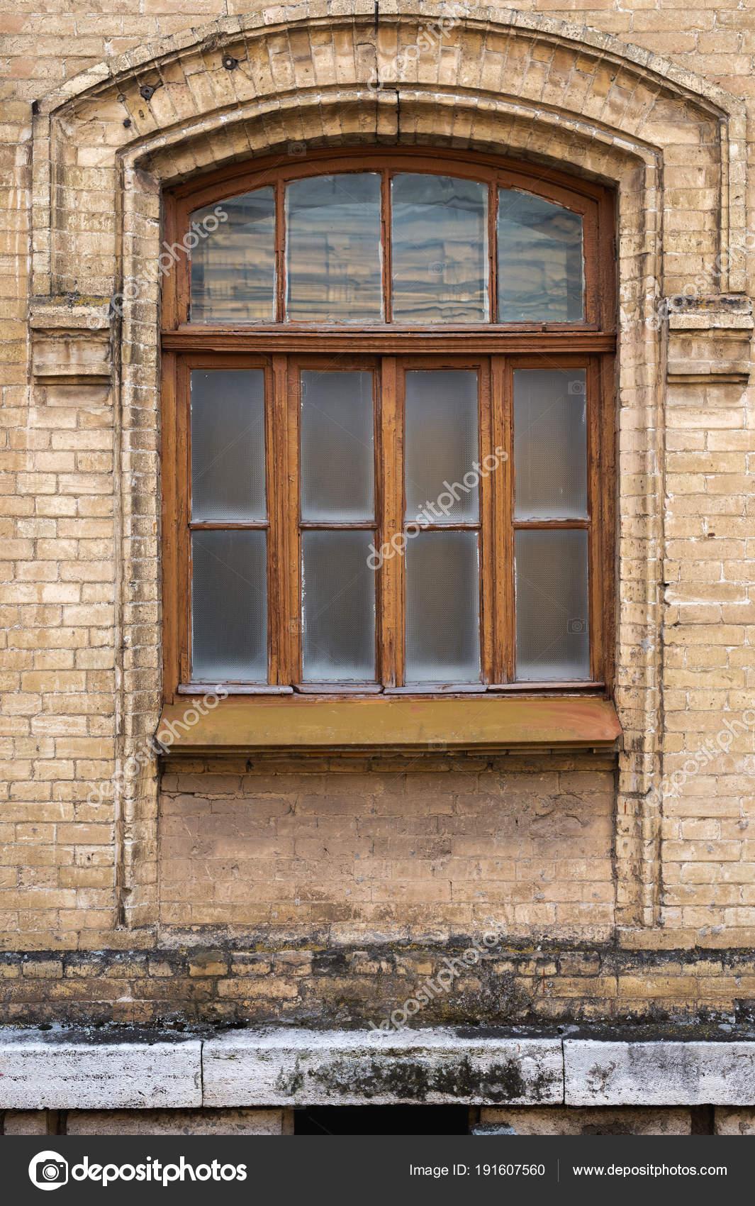 Ventana arqueada vintage en la pared de ladrillos amarillos. Cristal ...