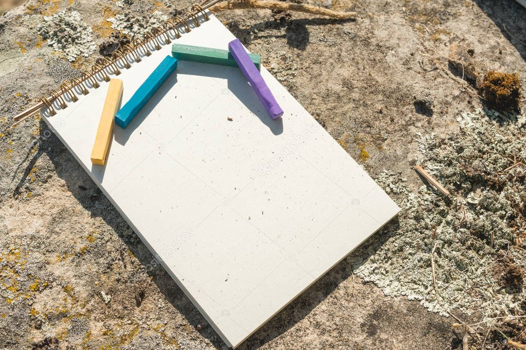Close-up artwork for the designer. A blank notepad for drawing pastel on which lay an artistic pastel crayons color chalks of purple green blue and yellow lies on a rock in nature outdoors. The