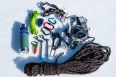 Nahaufnahme von Winterkletterausrüstung auf Neuschnee an einem sonnigen Tag. Carbinen mit einem Seilgarten und Zhumar sowie andere Anpassungen beim Winterbergsteigen. ganzjährige Anstiege zu