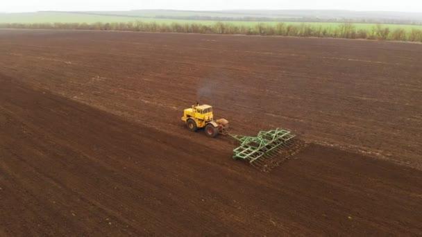 Letecký pohled na silný žlutý traktor s velkou námahou na háku provádějící orání orby pro setí zimních plodin s diskovým kultivátorem na podzim