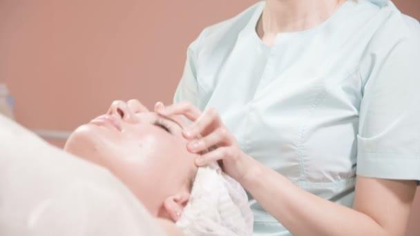 Close-up Spa masáž obličeje. Dívka profesionální masérka provádí relaxační masáž obličeje atraktivnímu klientovi lázeňského salonu
