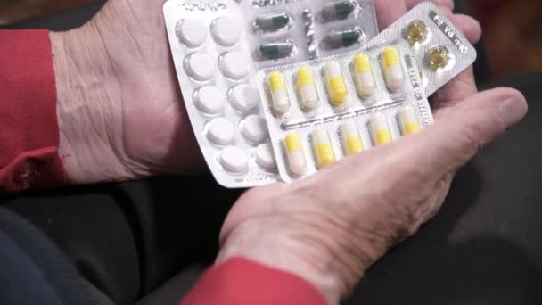 Closeup of a tablet on the hands of an old woman. The concept of choosing medication in old age