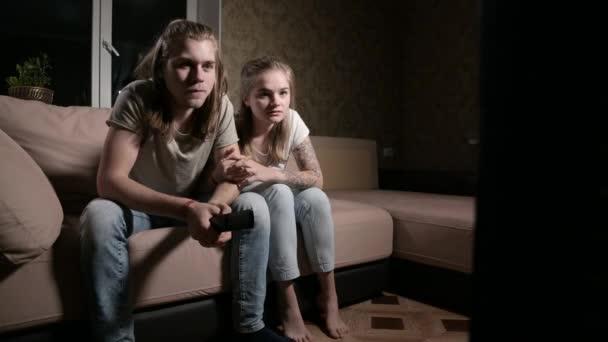 Mladý pár milénií sedí na gauči před televizí
