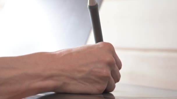 Close-up of a male designer draws on his laptop with help. graphic tablet and pen stylus