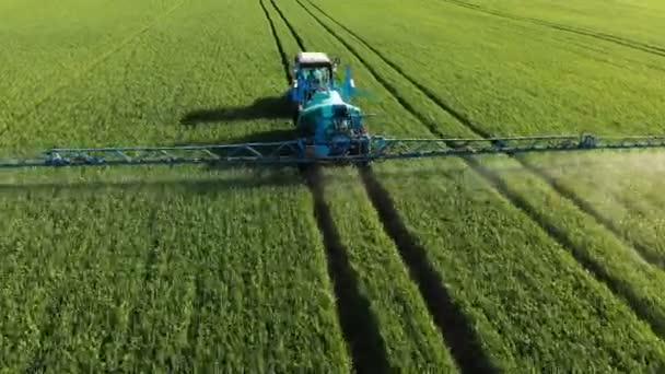 Letecký letoun. Modrý traktor jede na zeleném poli, zavlažuje rostliny.