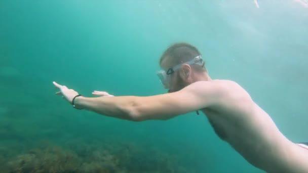 Ein hagerer Mann mit Bart und Maske schwimmt unter Wasser und fuchtelt mit den Armen. Nahaufnahme.