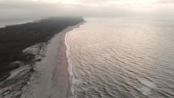 Luftaufnahme der Ostseeküste zur blauen Stunde nach Sonnenuntergang. Dämmerungsküste mit rollenden Wellen, leerem Strand und grauem Himmel
