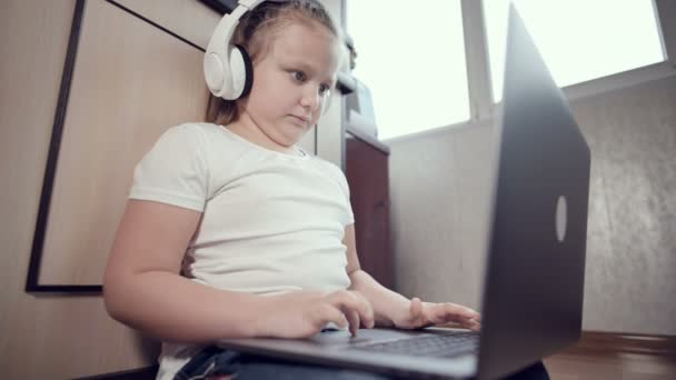 A smart little girl of seven years old in white headphones with a laptop in her hands is pushing on the floor in her room. The young generation on the Internet and IT technology