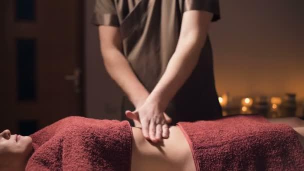 Střední střela mělká hloubka pole. Profesionální elitní masáž břišní anti-celulitidy a užitečná pro vnitřní orgány v tmavé masážní místnosti