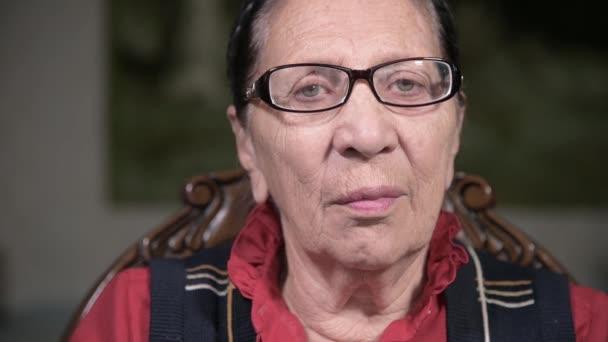 Portrét postarší zamyšlené ženy v brýlích opřené o paži, jak sedí a přemýšlí. Starší žena 80 let