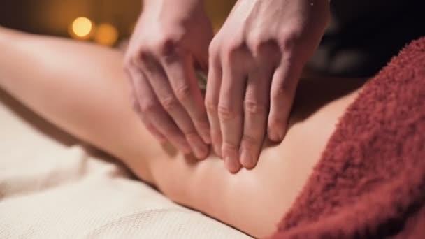 Prémium anti-cellulit combmasszázs közelről. Férfi kezek nem wellness masszázs a comb, hogy a beteg lány egy hangulatos tanulmány félhomályos fény. Luxusmasszázs