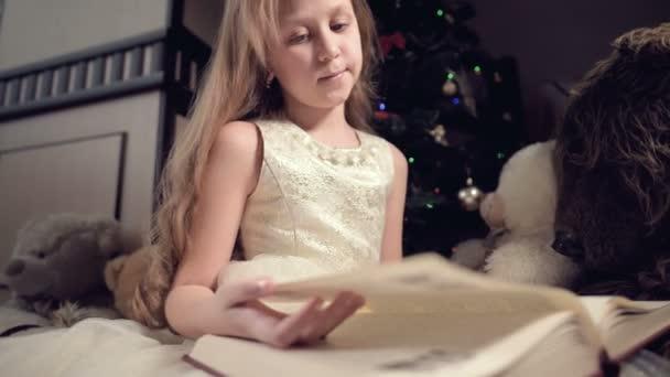 Malá blondýnka v svátečních šatech s knihou v ruce sedí vedle měkkých hraček na pozadí vánočního stromečku a čte knihu vedoucí stránku se svým místem.