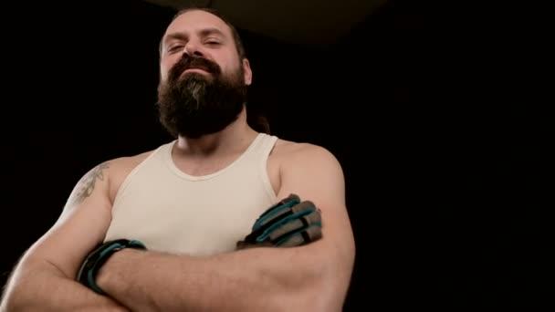 A szakállas férfi fekete háttérrel keresztbe teszi a karját, dühöt sugároz. Közelkép