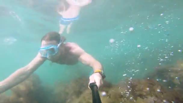 Ein muskulöser Mann mit Maske schwimmt unter Wasser und hält eine Kamera vor sich. Nahaufnahme.