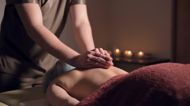Mladý masér provádí masáž zad ženě s tetováním v masážní místnosti s tlumenými světly na pozadí svíček. Koncept nízkoklíčové prémie masáže