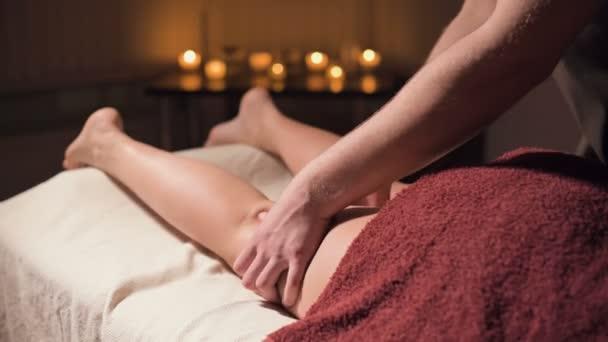 Nahaufnahme einer erstklassigen Anti-Cellulite-Schenkelmassage. Männliche Hände massieren in einer gemütlichen Studie mit schummrigem Licht den Oberschenkel der Patientin. Luxusmassagen