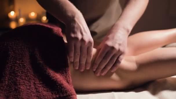 Detailní záběr prémiové masáže stehen proti celulitidě. Mužské ruce masírují pacientce stehno v útulné pracovně se slabým světlem. Luxusní masážní služby
