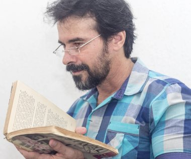 A white man with a black beard, some gray hairs, glasses, looking at a book, wearing a blue plaid shirt