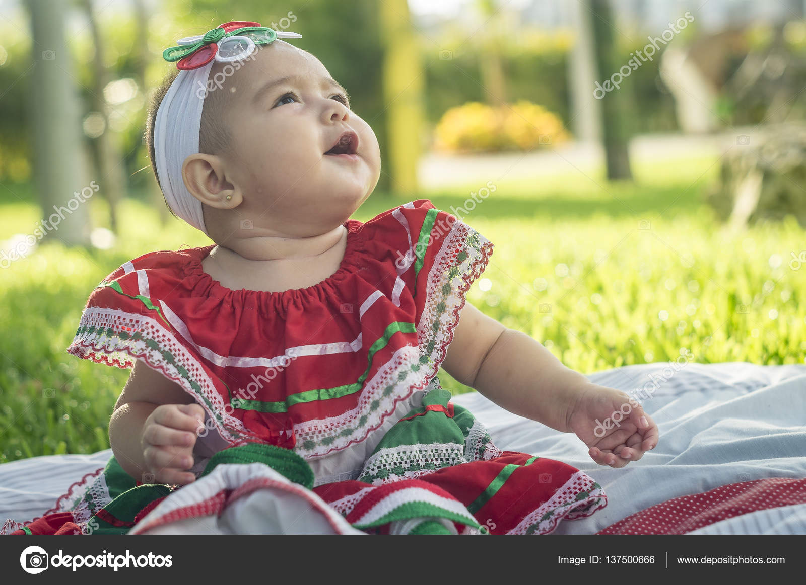 very beautiful white baby, sitting in the grass, wearing mexican